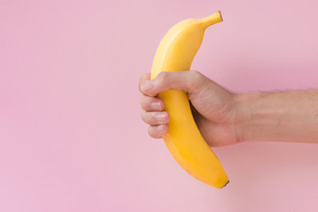 Male hand holding a banana isolated on pink background.