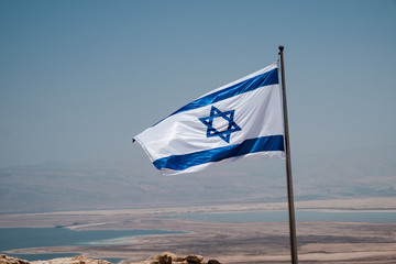 Israel flag waving in the wind on top of the masada fortress in Israel, a symbol of hope and a proof of our triumph