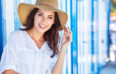 Portrait of a beautiful woman in a straw hat. Blue white background. sailor style