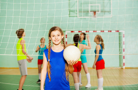 Happy teen girl with ball during training