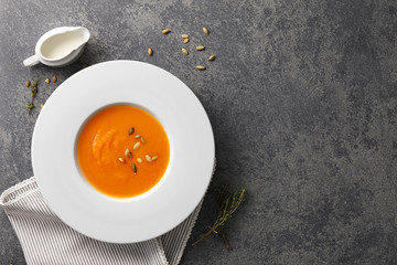 Pumpkin soup with seeds in a big white plate on gray stone background
