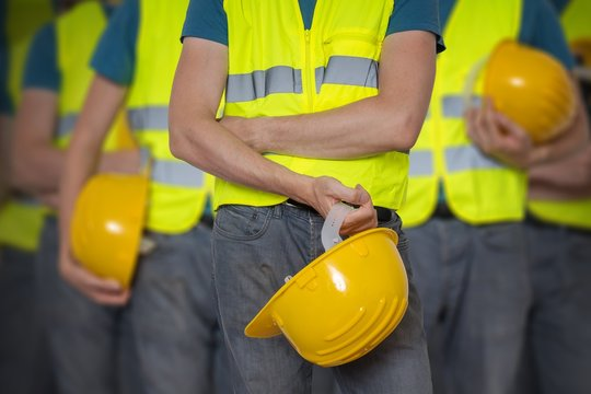 Many workers in vest with protective helmet.