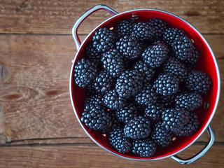 Blackberries in bowl on wooden background. Top view.