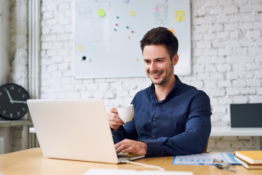 Joyful young startup businessman enjoying coffee and working on laptop in modern home office