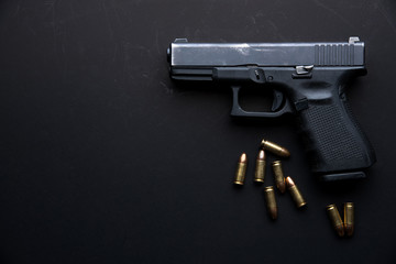 Gun with ammunition on dark table background.