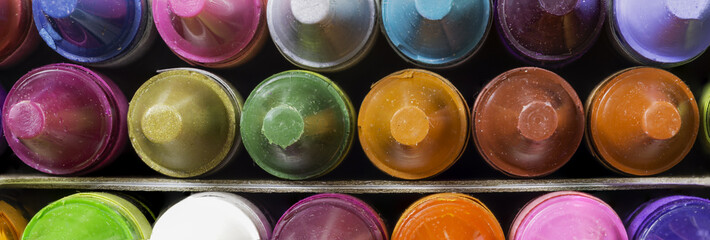 Wide closeup of new wax crayons on different colors