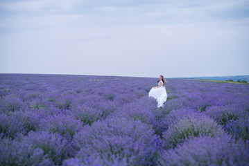 Young girl in white dress in lavender field