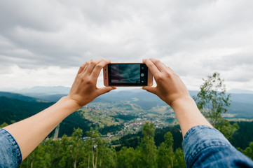 Closeup of tan women hands holding mobile phone with wide touchscreen and making photos and video of beautiful nature landscape from high altitude in mountains.  Low cloudy sky. Travel and dicover.