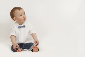 little boy reading a book sitting on a white background