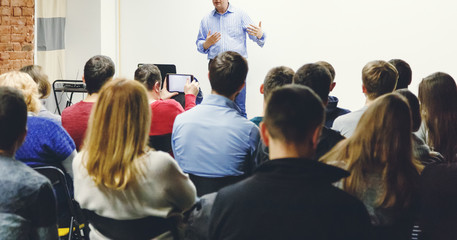Adult students listen to professor's lecture in small class room. Panoramic aspect ratio.