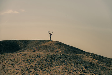 Man with camera and winner gesture on desert hill top