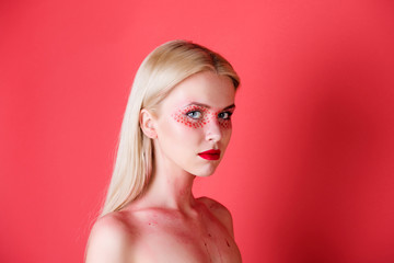 woman with creative fashionable makeup on red background