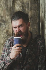 Brutal bearded hipster holding plastic coffee cup