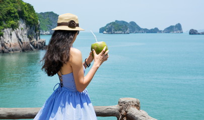 Girl holding coconut by the seaside