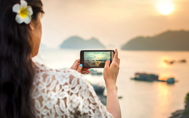 Girl taking seaside sunset picture with smartphone
