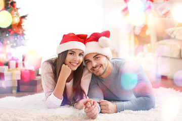 Young couple in Santa Claus hats indoors