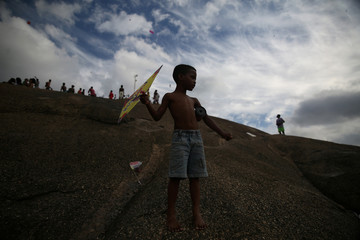 A boy waits for a wind to fly a kite during a kite battle at a slum in Niteroi