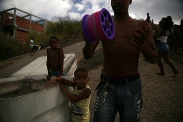 A teenager rolls a kite line reel during a kite battle at a slum in Niteroi