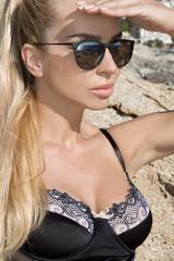 Beautiful female model, standing in sexy bikini on in the sea at the beach