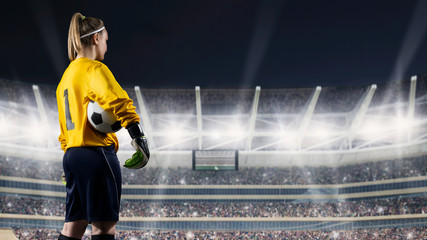 female goalkeeper standing with the ball against the crowded stadium at night