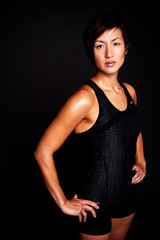Fit Asian woman isolated on black.