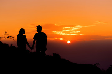Silouette couple holding hand and look together at sunset.