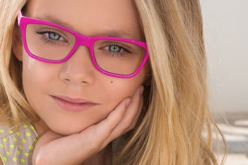 Portrait of a cute little girl with glasses on the background of the sea