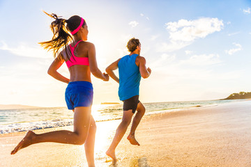 Runners fitness couple running training on beach. Morning cardio workout people doing exercise. ctive sports lifestyle.