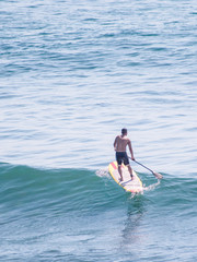 A guy is doing paddle boarding at ocean