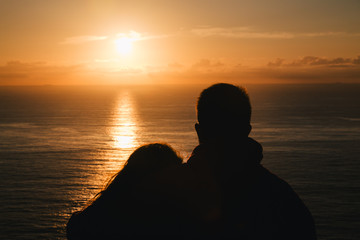 Romantic couple watching the sunset in the ocean. Silhouette
