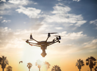 Holidays with a copter: a drone with a camera flying on a beautiful sunset sky with palm trees on the background.