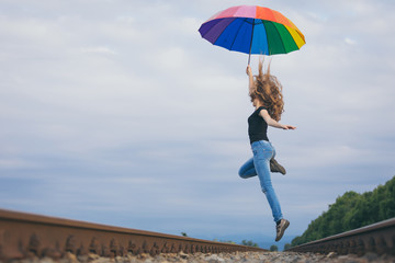Teen girl with umbrella jumping on the railway at the day time.