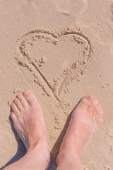 woman feet on sand with the hart image drawn on sand