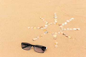 abstract sun image made of seashells on a sand with sunglasses