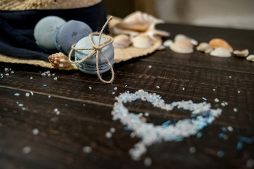 Straw hat with blue macaroons and sea salt with shells on the wood background