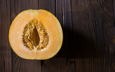 Melon cut in half on a wooden background (Top view)