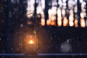 Vintage style lamp with a candle at snowy winter night