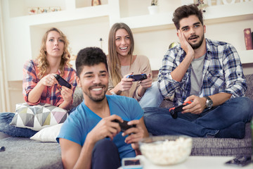 Friends playing video games at home