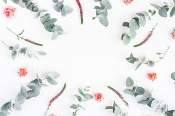 Flowers composition. Round frame made of rose flowers and eucalyptus branches on white background. Flat lay, top view, copy space