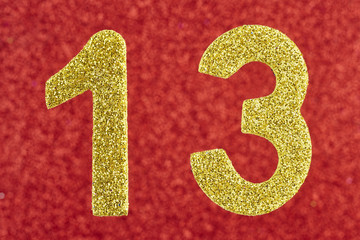 Number thirteen golden color over a red background. Anniversary.