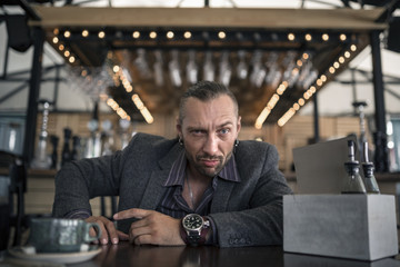 angry smiling businessman sitting at the table in cafe having the coffee-break drinking cup of tea and looking on you.