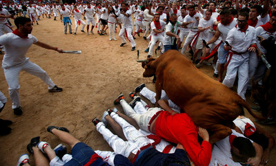 A wild cow leaps over revelers in the bull ring following the fourth running of the bulls at the San Fermin festival in Pamplona