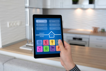 man hand holding tablet app smart home background room kitchen
