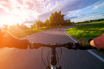 Riding a bike first person perspective. Olympic bicycle road towards sun.