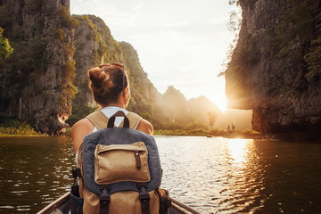 woman with backpack traveling by boat enjoying sunset among of mountains.