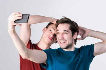 Two happy friends taking selfie on mobile phone camera