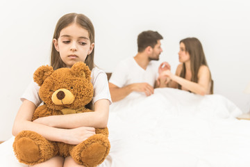 The sad girl with a toy sit near parents on the bed