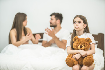 The girl with a soft toy sitting near the parents in the bed