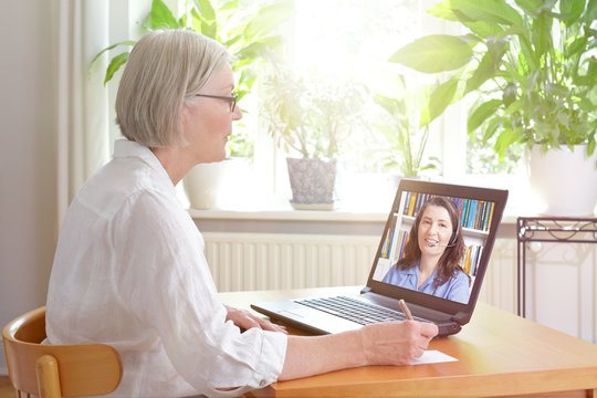 E-learning concept: senior woman at home in front of her laptop making notes while watching a live english language lecture by a female teacher.