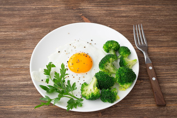 Keuken foto achterwand Gebakken Eieren Fried eggs with broccoli and greens. Delicious homemade breakfast. On a wooden table, selective focus